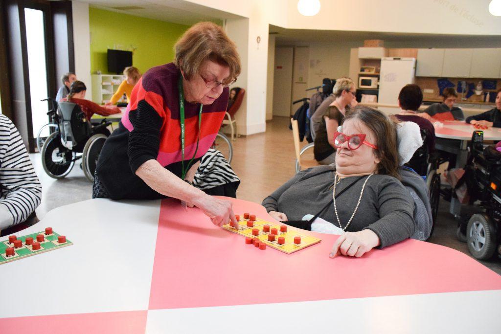 Une bénévole aidant une résidente de la Mosaïque lors du loto
