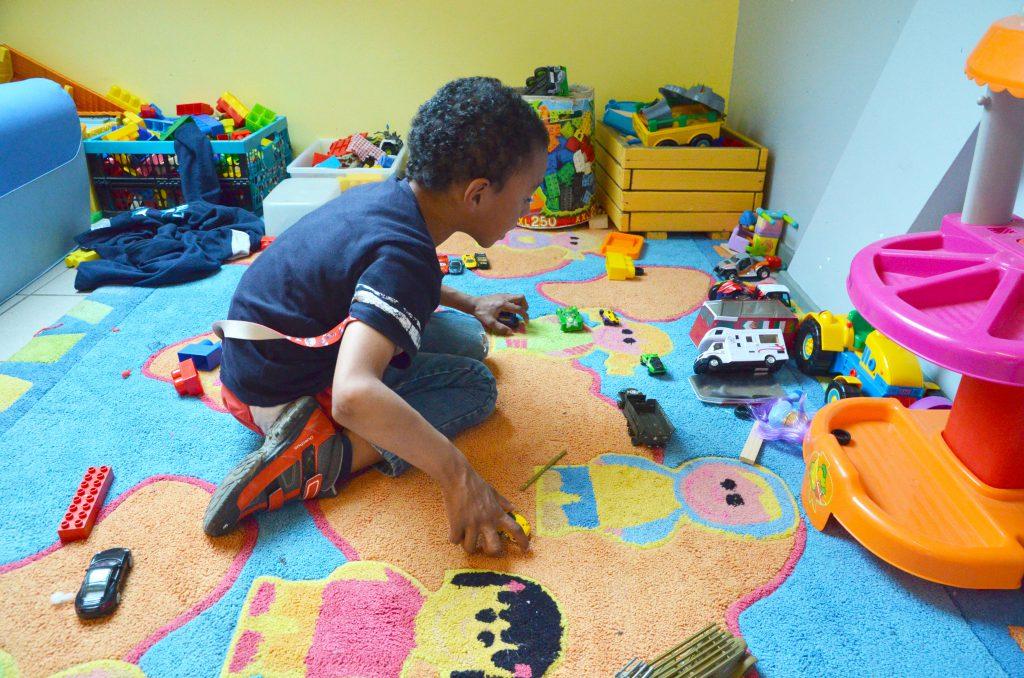 Petit garçon jouant aux petites voitures sur un tapis coloré