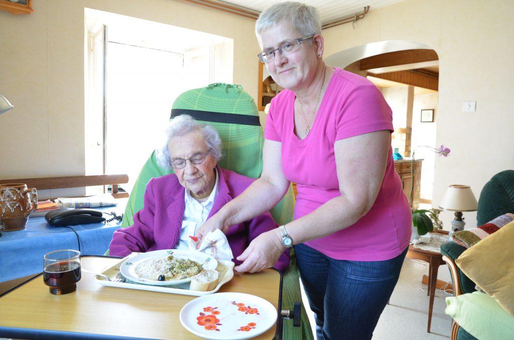 Une aide à domicile accompagne une usagère pour son repas