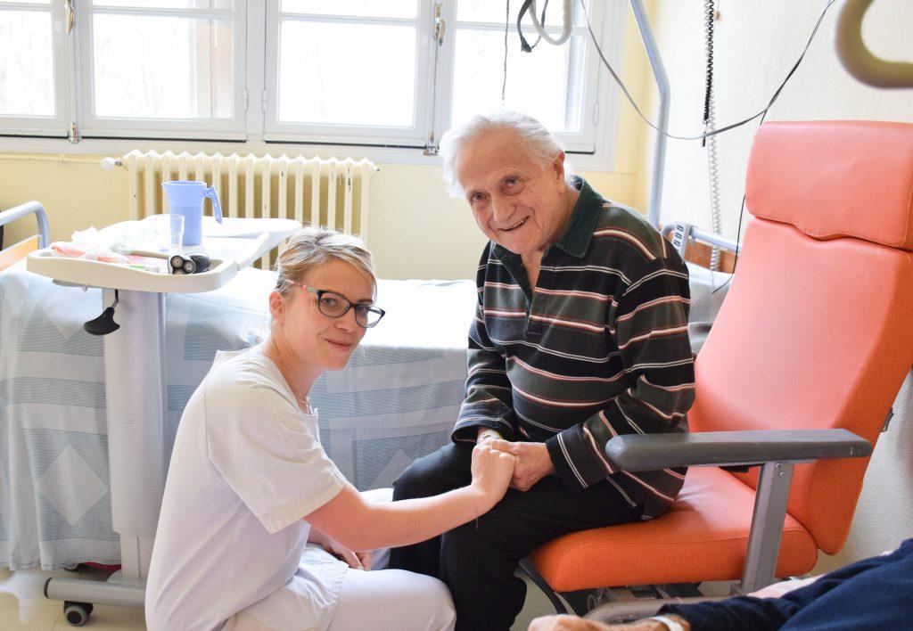 Une infirmière est accroupie et tient la main d'un patient installé sur le fauteuil de sa chambre.
