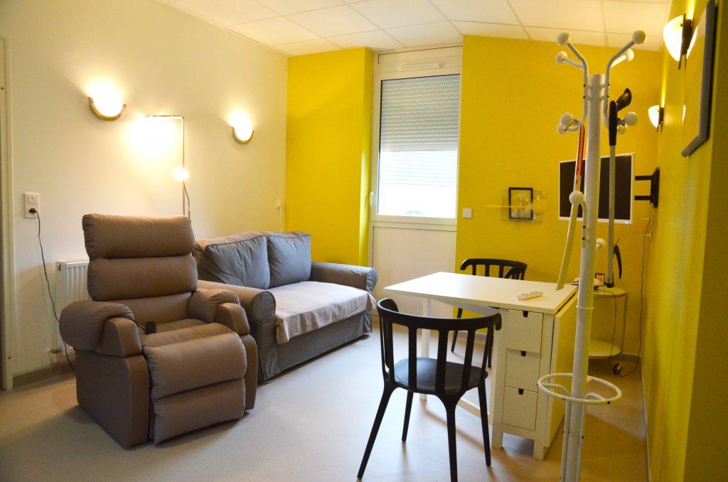 Fauteuil releveur, canapé, table, télévision, porte manteaux, chausse-pied, compose le salon de la maison des capacités