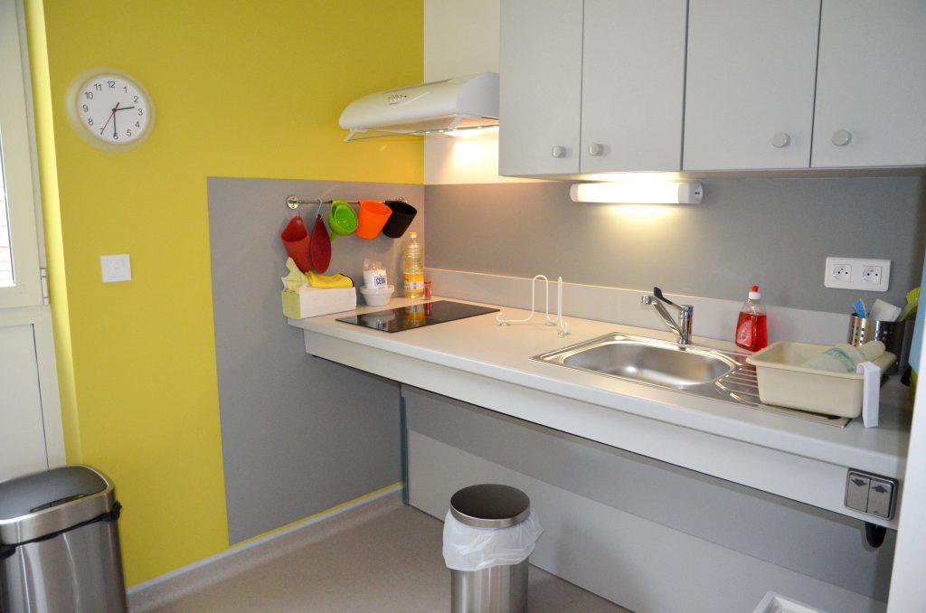 Plan de travail ajustable de la cuisine de la Maison des capacités avec plaques de cuison et évier