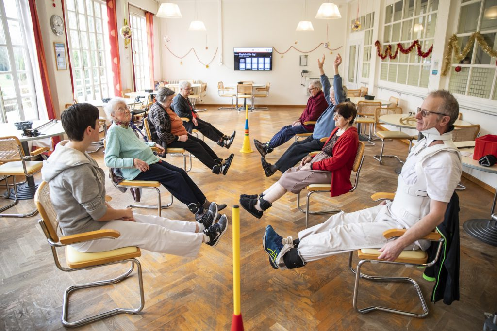 7 personnes encadrées par une rééducatrice sont assis et lève leurs jambes lestées par des poids.