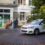 Une patiente en fauteuil roulant accompagnée de deux personnes du service de taxi médical (VSL) s'appretent à rentrer à la Clinique Médicale Brugnon Agache.