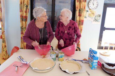 Deux dames se regardant et préparant une tarte